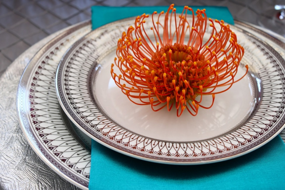 teal napkin with orange/red protea